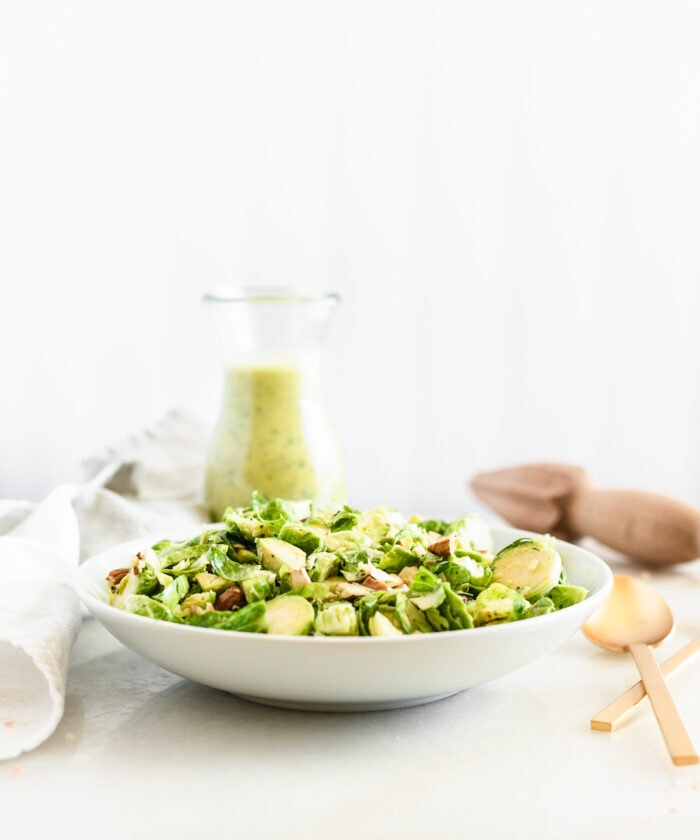 shaved brussels sprouts salad in a white bowl with a glass bottle of citrus shallot dressing behind it.