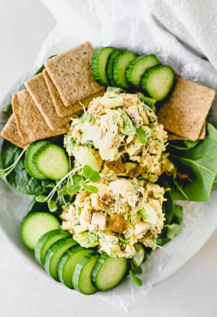 overhead view of no-mayo coconut curry chicken salad on a white plate with sliced cucumbers, crackers, and leafy greens.