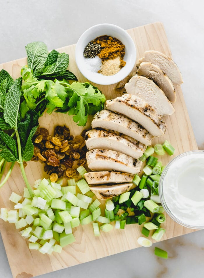 overhead view of ingredients needed to make mayo-free coconut curry chicken salad on a cutting board.