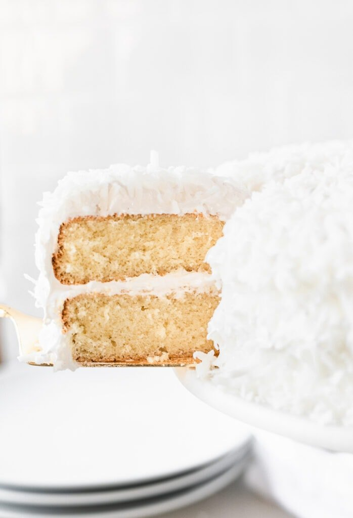 slice being removed from a coconut cake with 7 minute frosting.
