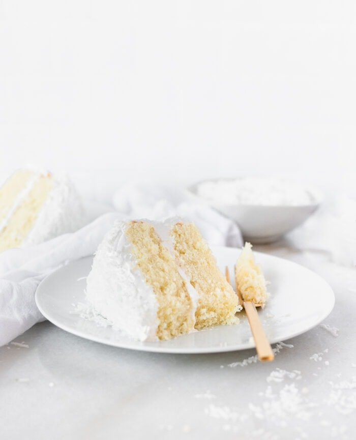 slice of coconut cake on a white plate with a bite taken out with a gold fork.
