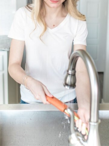 woman in a white shirt washing carrots at the sink.
