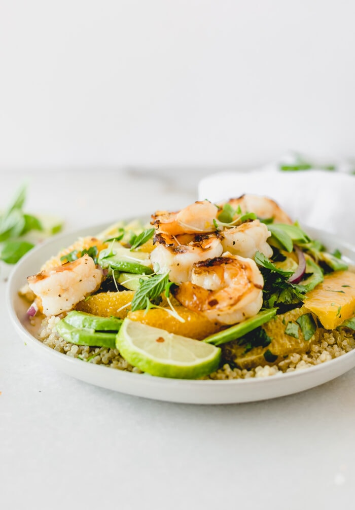 Shrimp, Orange and Avocado Quinoa Salad on a grey plate with lime wedges and herbs.