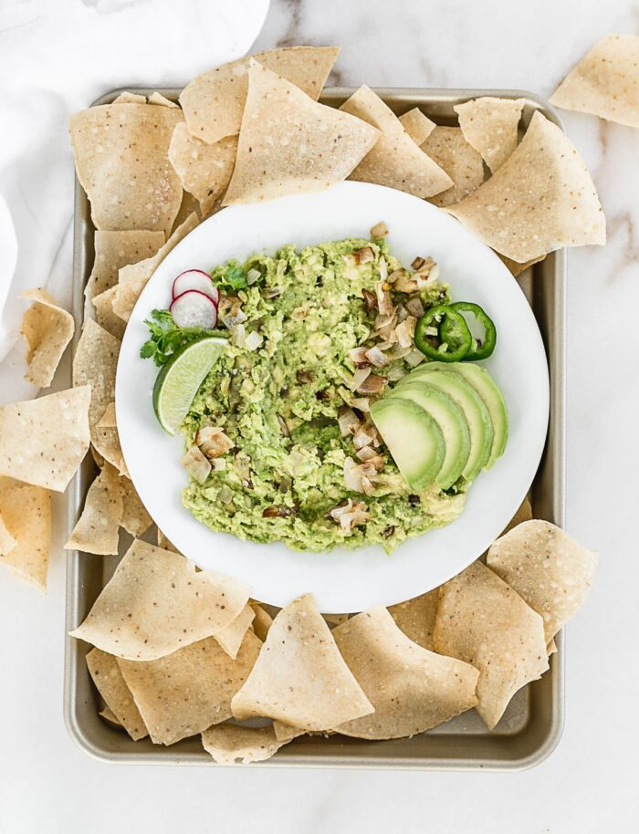 Caramelized onion guacamole on a plate with chips.