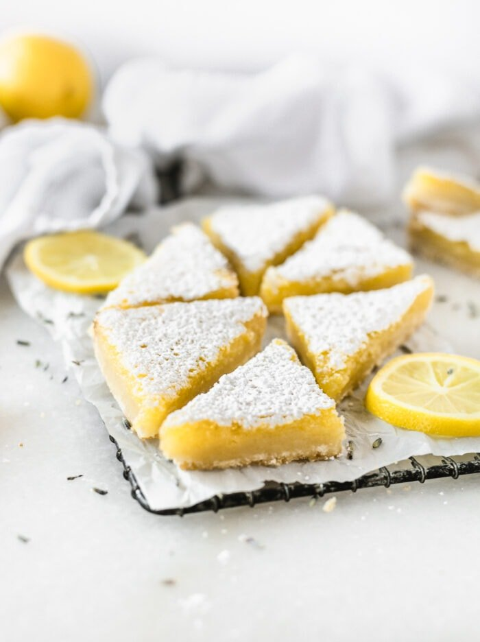 lavender lemon bars cut into triangles on a wire rack surrounded by lemon slices.