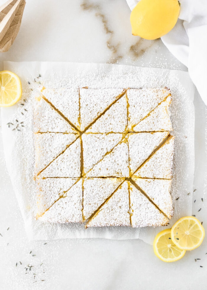 overhead view of lavender lemon bars cut into triangles surrounded by lemon slices and dried lavender.