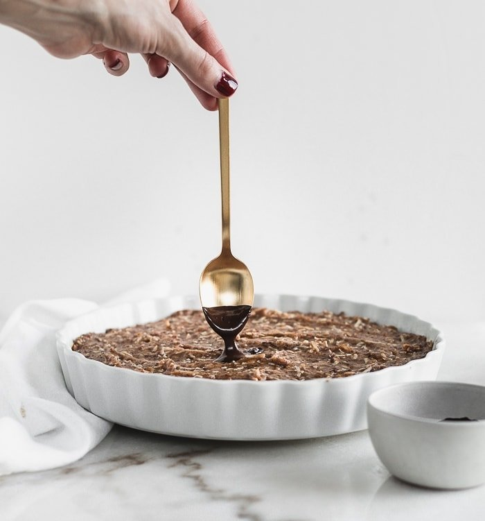 hand spooning melted chocolate onto baked oatmeal topped with coconut caramel.