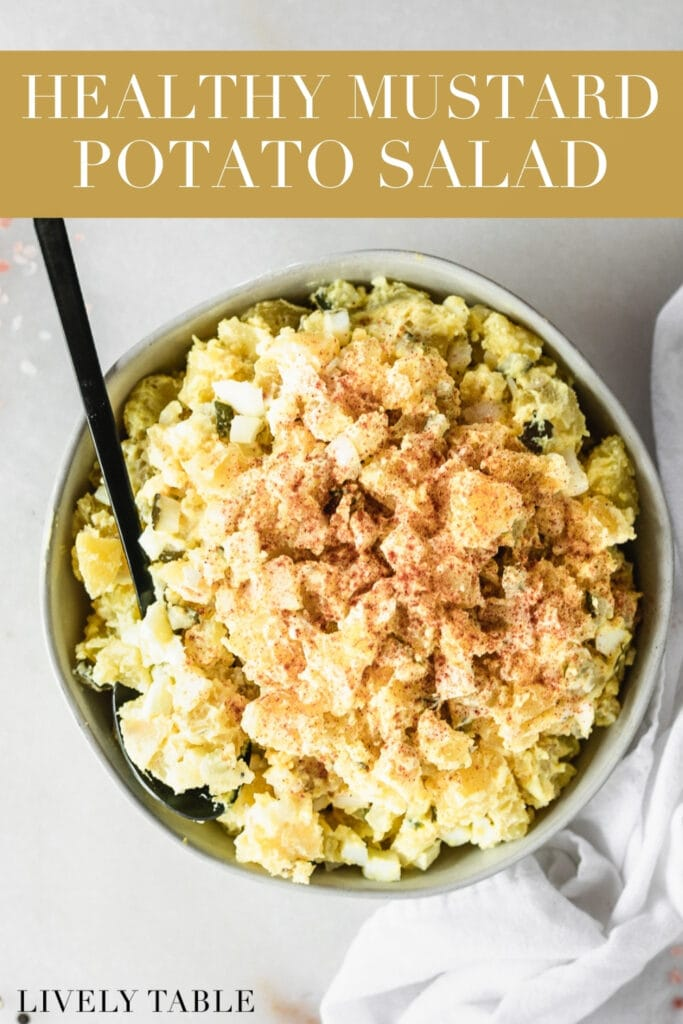 overhead view of mustard potato salad sprinkled with paprika in a grey bowl with a black spoon in it with text overlay.
