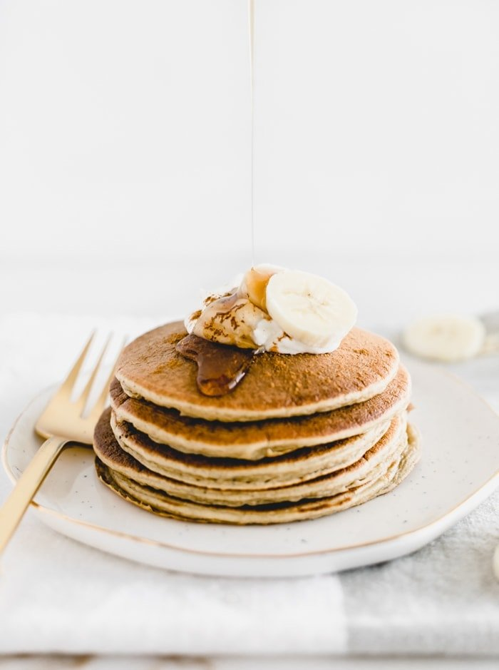 stack of Gluten Free Banana Chai Blender Pancakes on a white plate with syrup being poured on top.