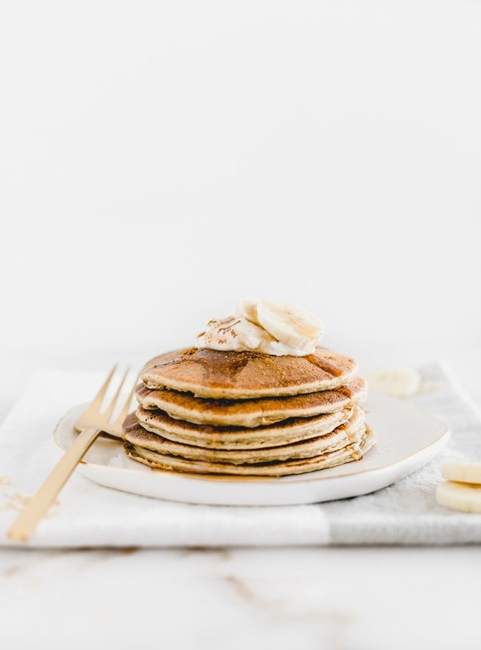 stack of Gluten Free Banana Chai Blender Pancakes on a white plate with a gold fork.