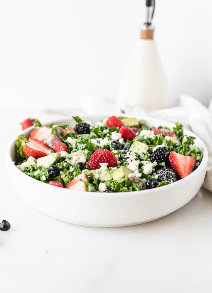 berry avocado kale salad in a white bowl with a bottle of olive oil in the background.