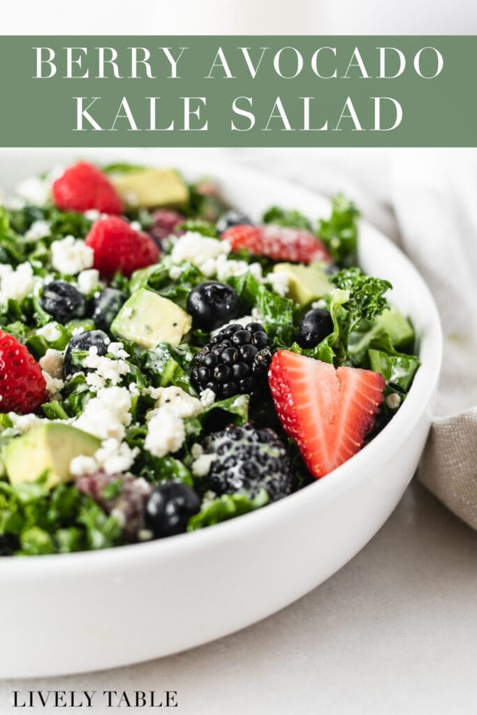 closeup of berries on a berry avocado kale salad in a white bowl with text overlay.