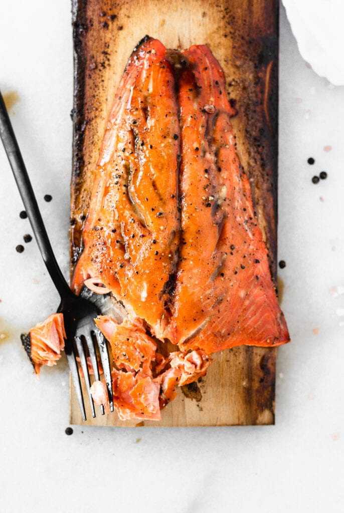 overhead view of grilled bourbon glazed salmon on a cedar plank with a black fork.