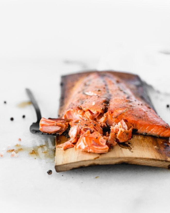 grilled bourbon glazed salmon on a cedar plank with a black fork cutting away a piece.