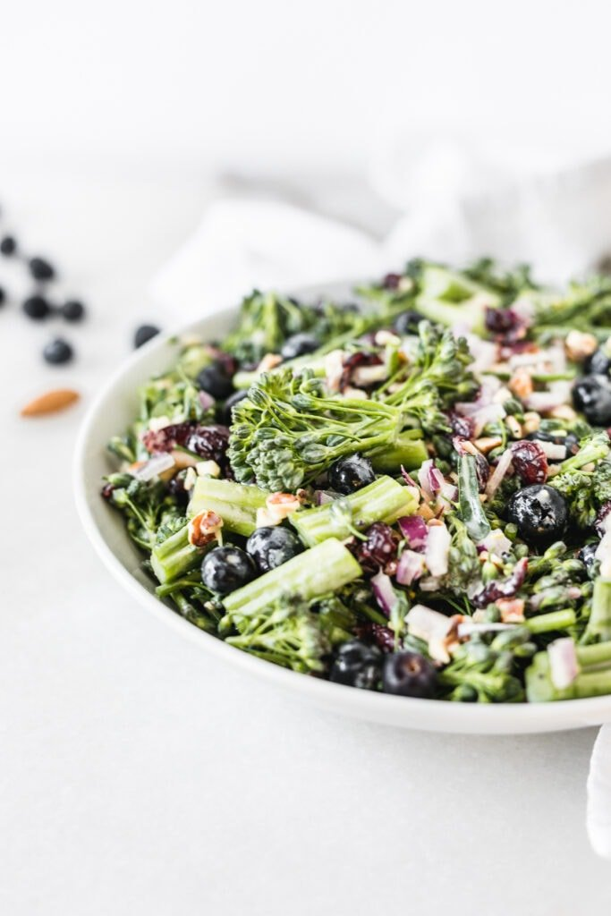closeup of broccolini superfood salad in a white bowl.
