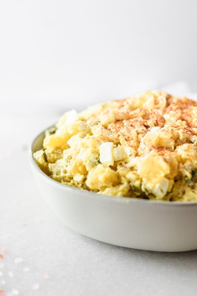 closeup of healthy mustard potato salad in a grey bowl.