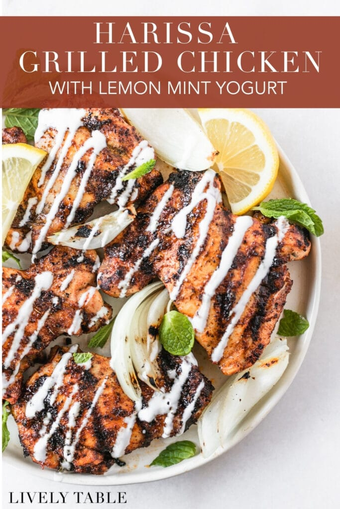 overhead view of harissa grilled chicken thighs with lemon mint yogurt sauce drizzled over the top with text overlay.