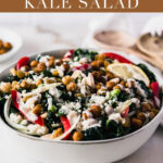 This flavorful Moroccan chickpea kale salad, with seasoned roasted chickpeas, bell pepper, raisins, almonds, and feta is anything but boring! It's a great make-ahead salad for work lunches or a delicious side dish. #glutenfree #vegetarian #vegan #dairyfreeoptionv#sidedish #moroccanrecipe #kalesalad #salads #chickpea