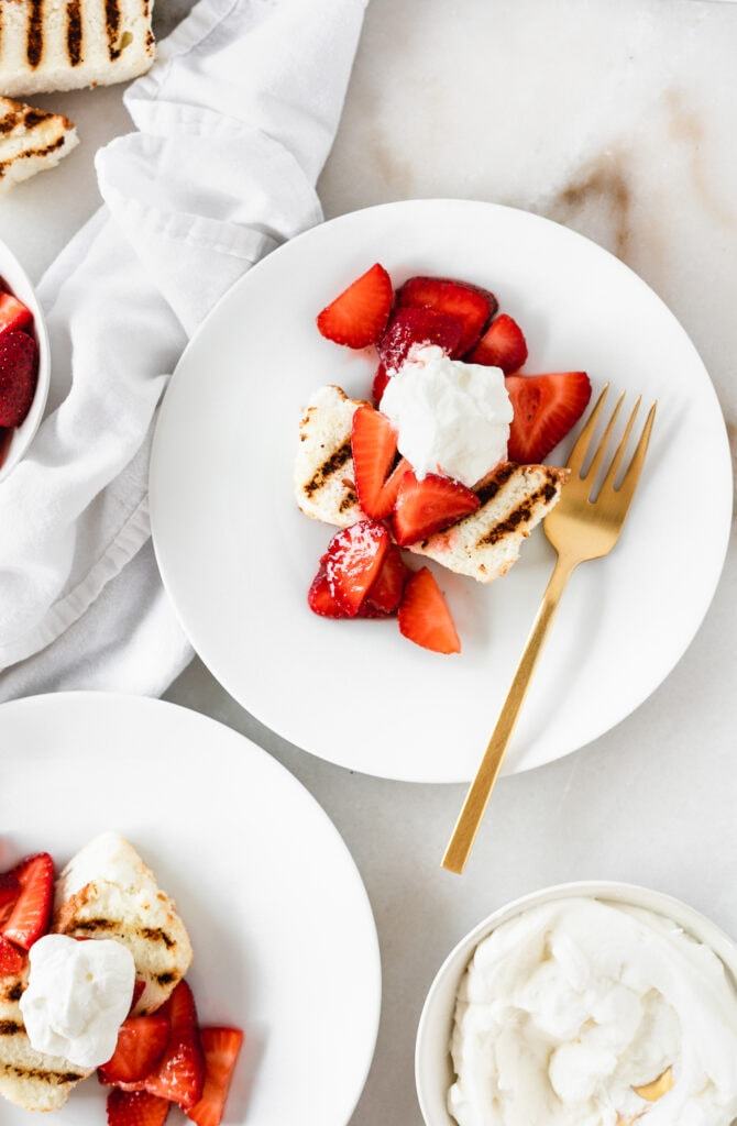 overhead view of grilled angel food cake topped with strawberries and whipped cream on a white plate with a gold fork.