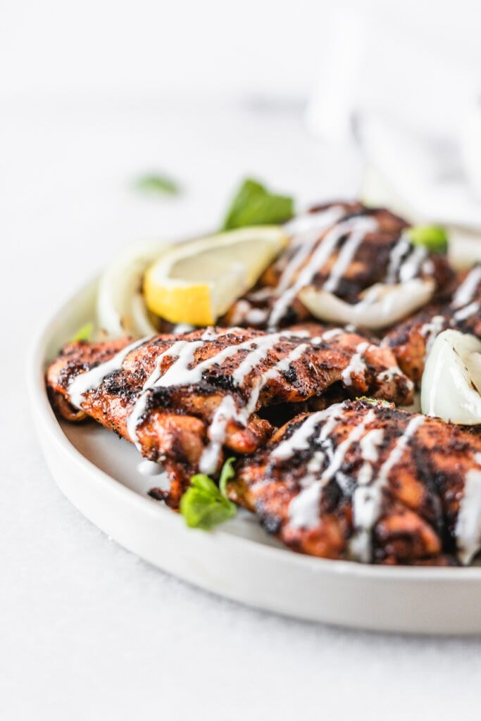closeup of harissa grilled chicken thighs with lemon mint yogurt sauce drizzled over the top.