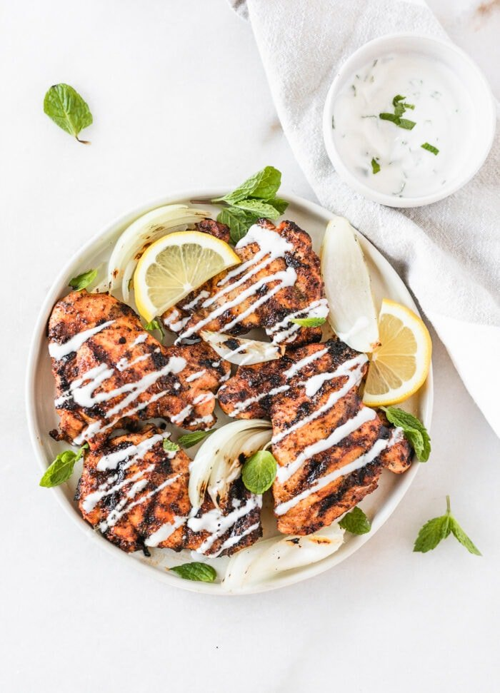 overhead view of harissa grilled chicken thighs with lemon mint yogurt sauce on a white plate with a bowl of sauce next to it.