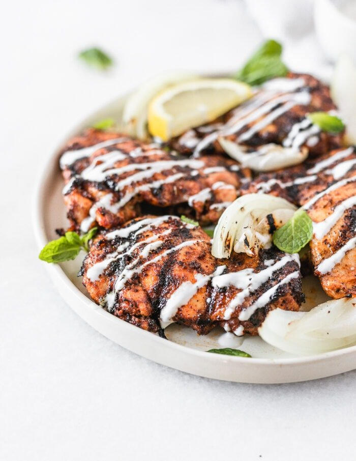 harissa grilled chicken thighs and onions with lemon mint yogurt sauce drizzled over them on a white plate.