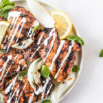 overhead view of harissa grilled chicken thighs with lemon mint yogurt sauce drizzled over the top.