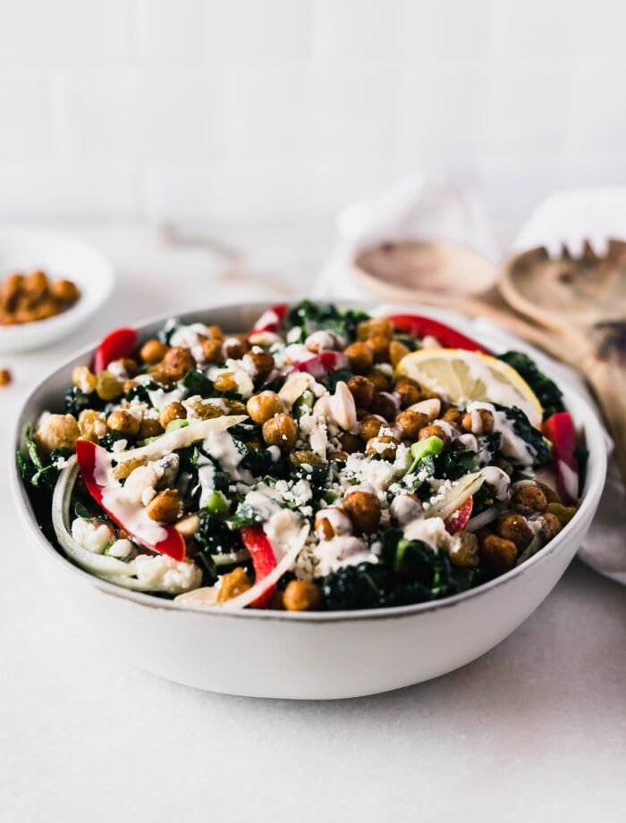 Moroccan chickpea kale salad drizzled with tahini dressing in a grey bowl.