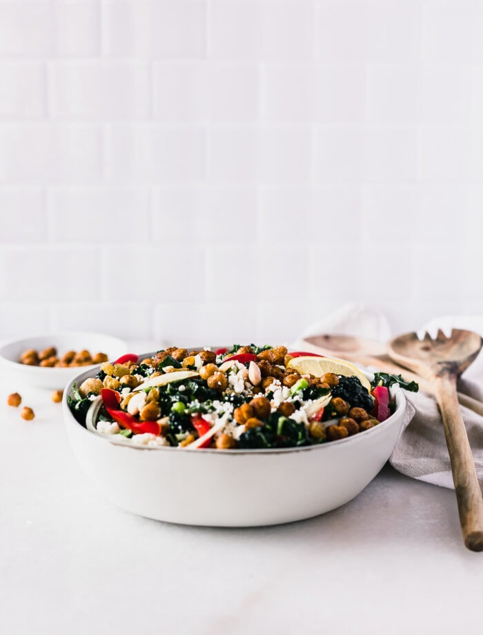 moroccan chickpea kale salad in a gray bowl with wooden spoons next to it.