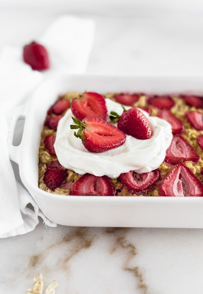 Close up of strawberry baked oatmeal in a white baking dish.