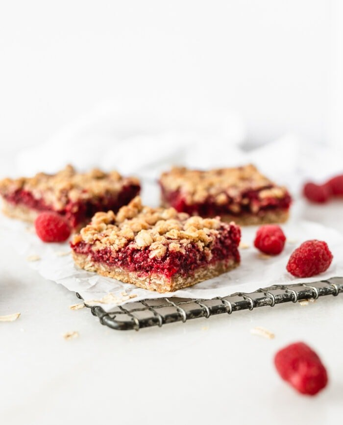 Raspberry Oat Crumble Bars on a wire cooling rack with oats and raspberries scattered around them.