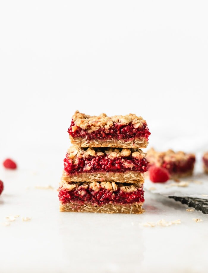 3 Raspberry Oat Crumble Bars stacked on top of each other.