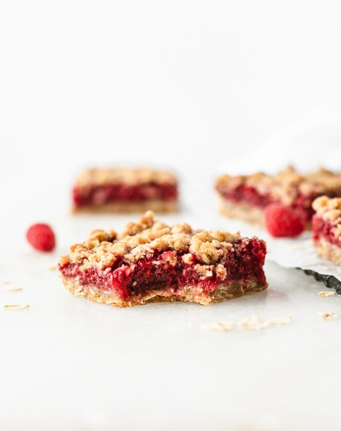 Raspberry Oat Crumble Bar with a bite taken out of the corner.