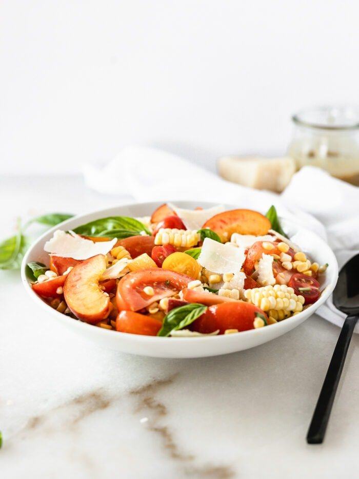 corn peach and tomato basil salad with parmesan in a white bowl with a black spoon beside it.