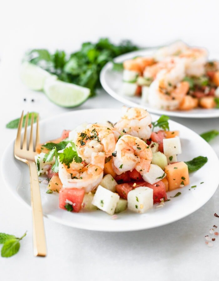 grilled shrimp and jicama melon salad on a white plate with a gold fork.