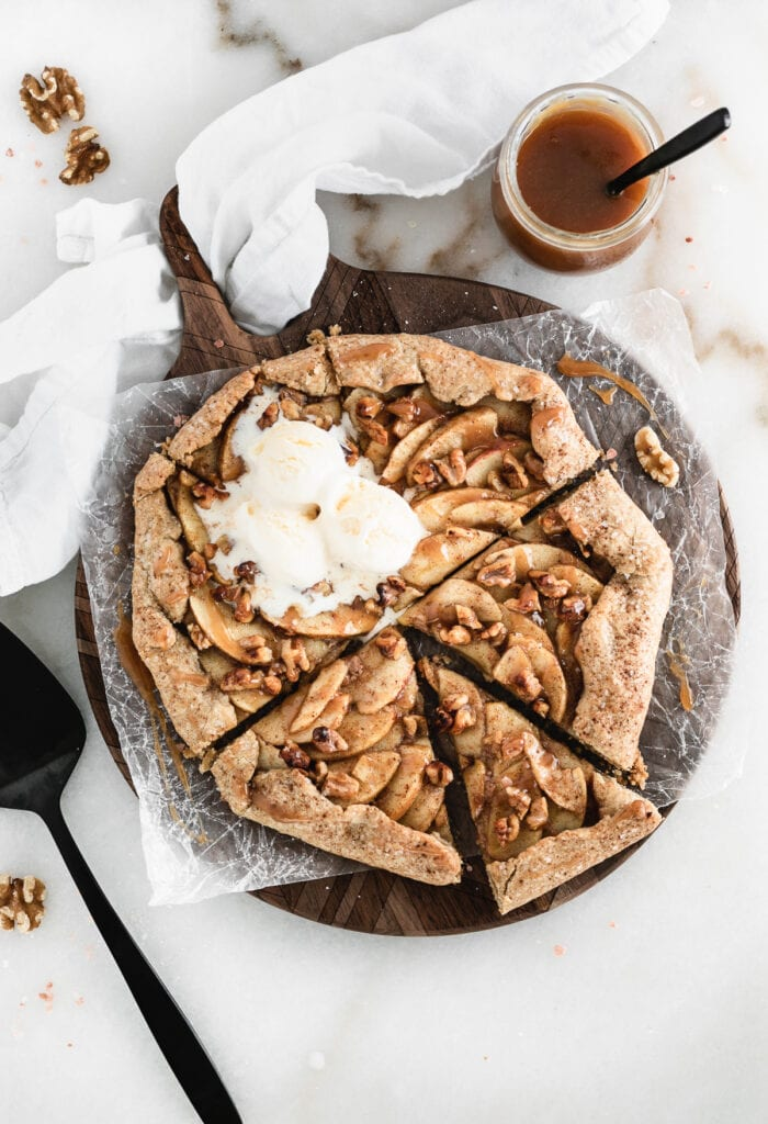 overhead view of sliced caramel apple walnut galette with ice cream on top on a round wooden board.