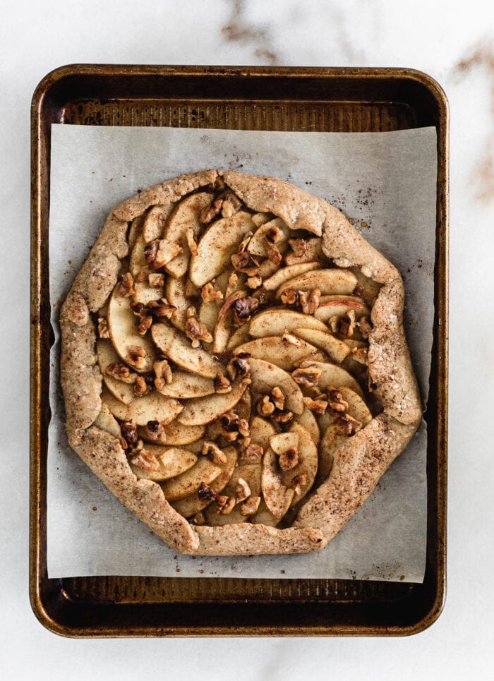 overhead view of baked caramel apple galette on a parchment lined baking sheet.