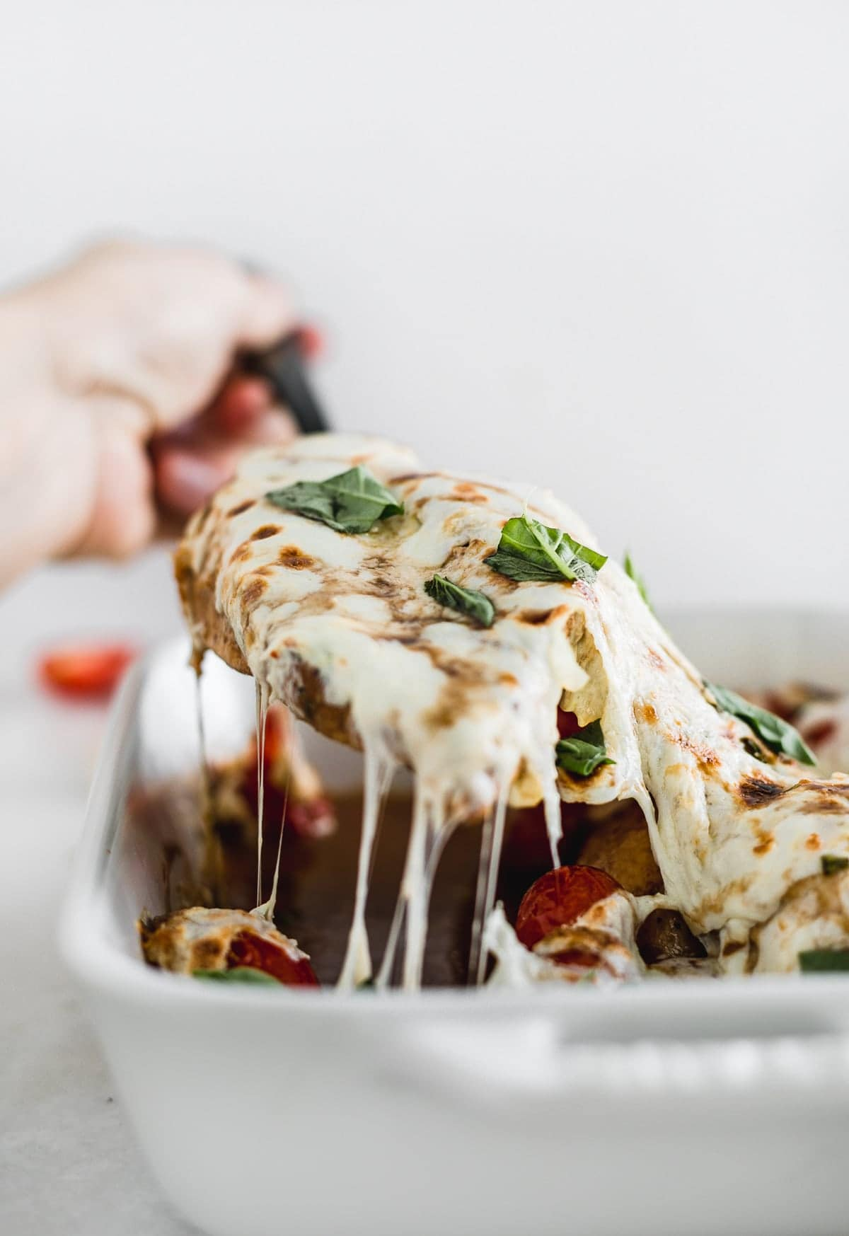 Grabbing a piece of easy oven baked Caprese chicken.