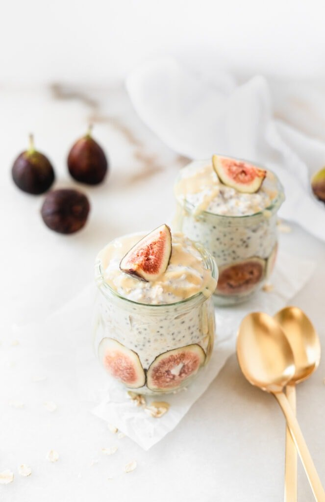 two jars of maple tahini fig overnight oats with two gold spoons beside them.