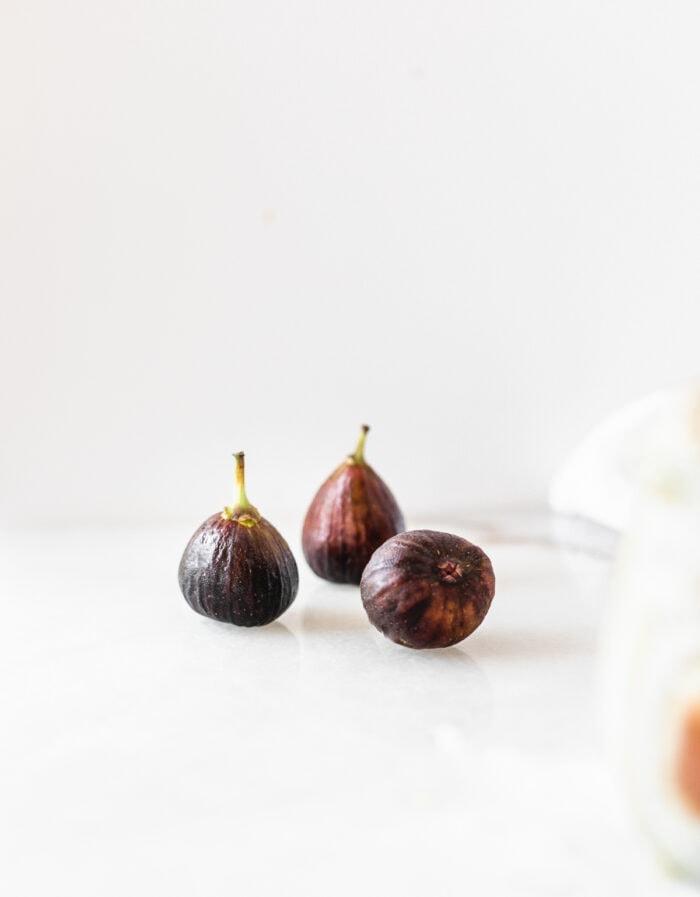 three fresh figs on a white background.
