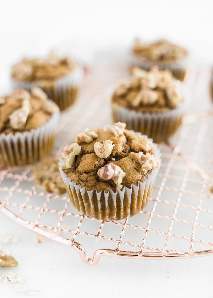 maple walnut pumpkin muffins on a round rose gold wire cooling rack.