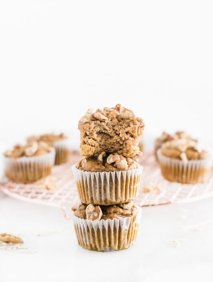 three maple walnut pumpkin muffins stacked on top of each other, the top muffin has a bite taken out.