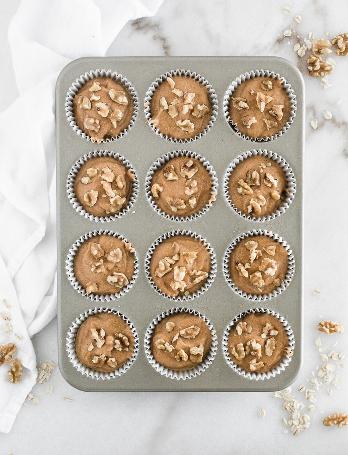 overhead view of pumpkin muffin batter in a muffin tin with walnuts on top.
