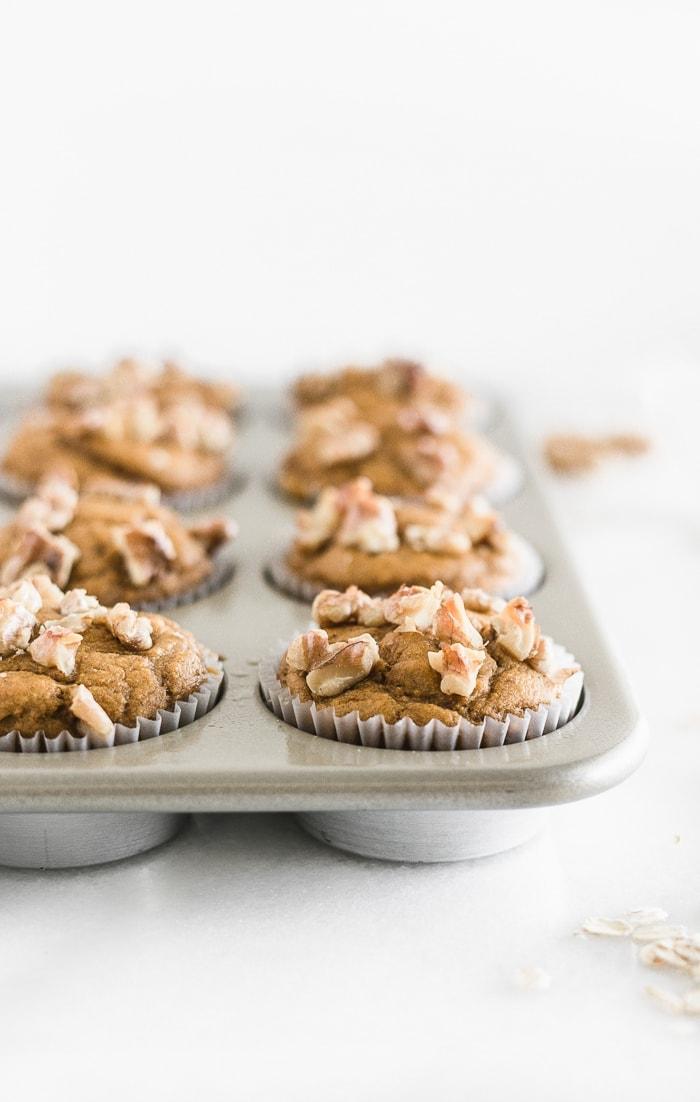 close up of gluten free maple walnut pumpkin blender muffins in a muffin tin