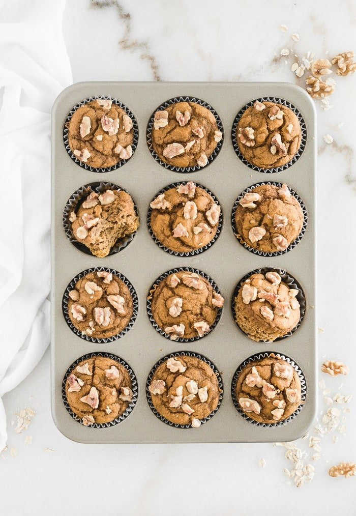 overhead view of maple walnut pumpkin muffins in a muffin tin.