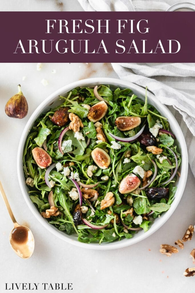 overhead view of fig arugula salad in a white bowl with text overlay.