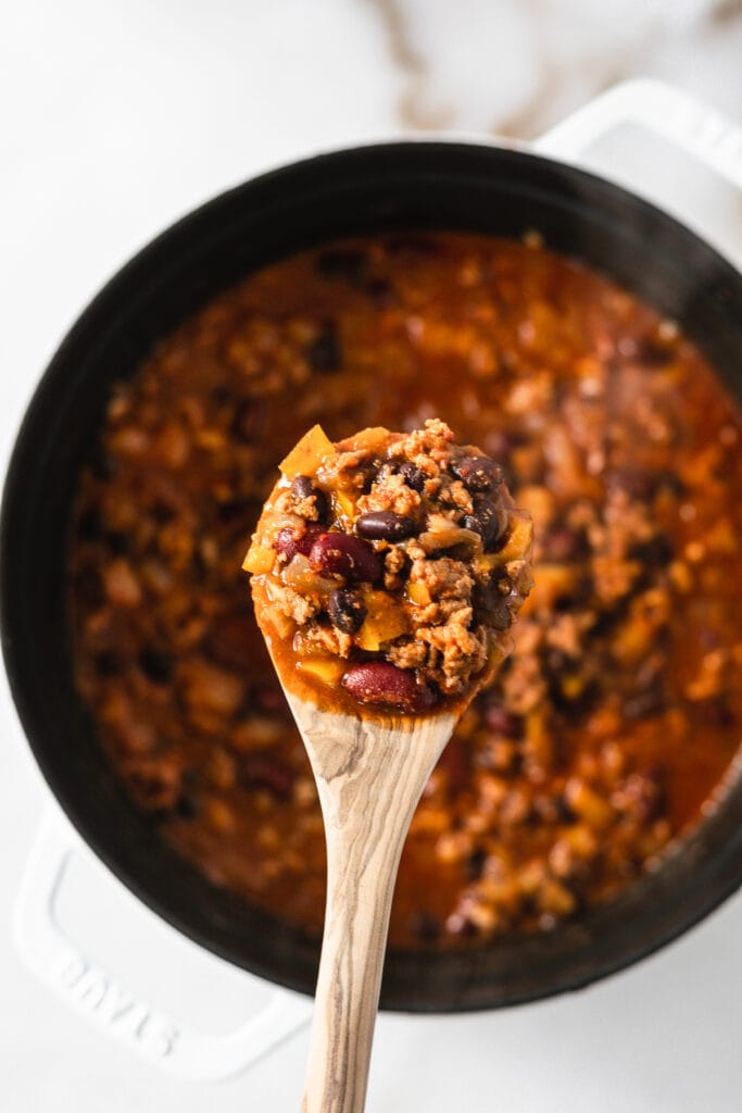 wooden spoon lifting apple turkey chili out of a pot.