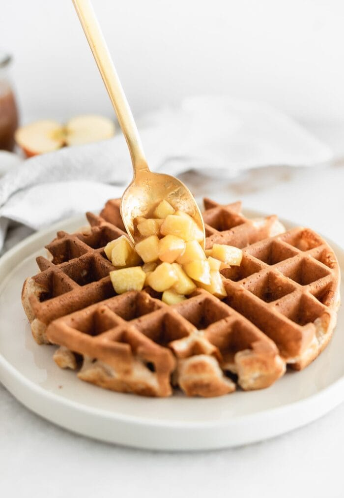 gold spoon placing caramel apple topping onto a waffle on a white plate.
