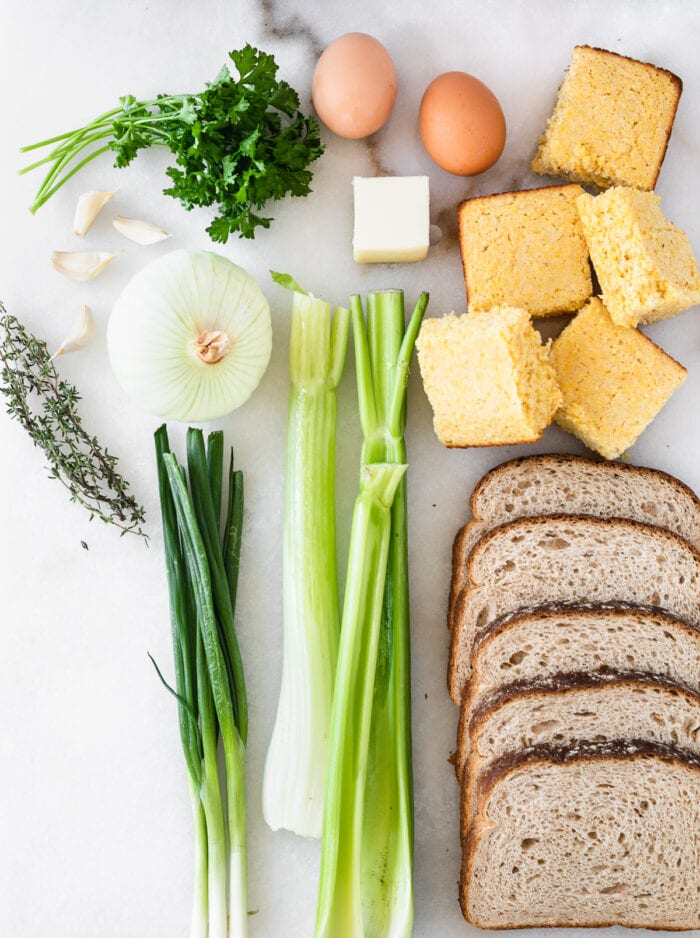 overhead view of ingredients needed to make southern cornbread stuffing on a white background.