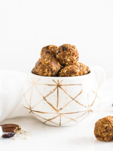 healthy pumpkin protein balls with pecans and cranberries stacked in a white and gold mug.